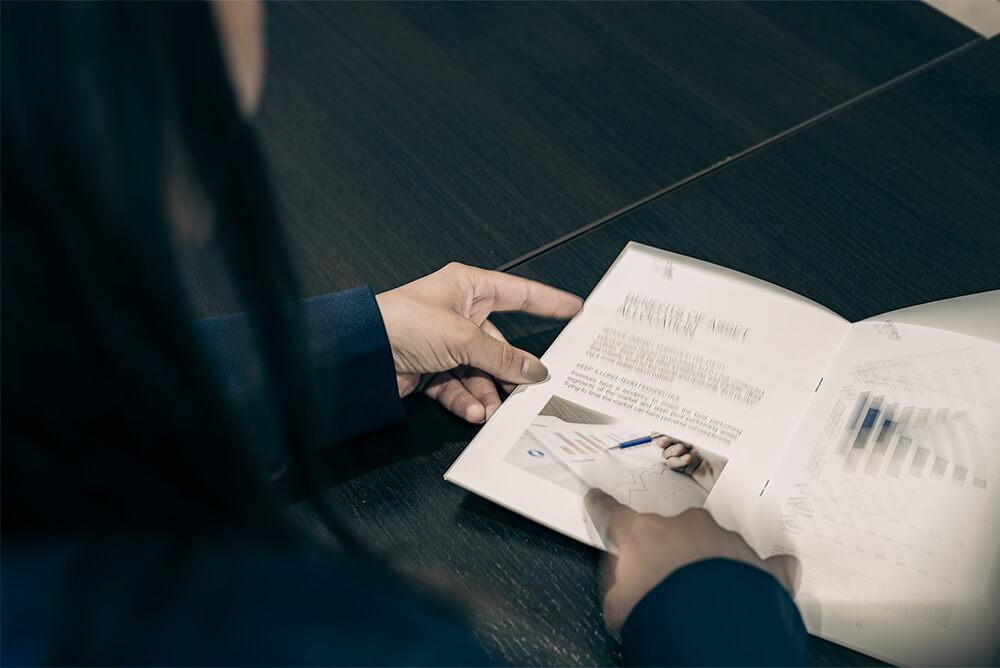 Personne feuilletant un prospectus de SG M&R dans leurs bureaux.
